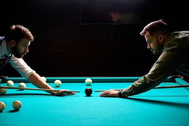 Zwei junge männliche freunde kamen, um nach der arbeit im dunklen club billard oder snooker zu spielen