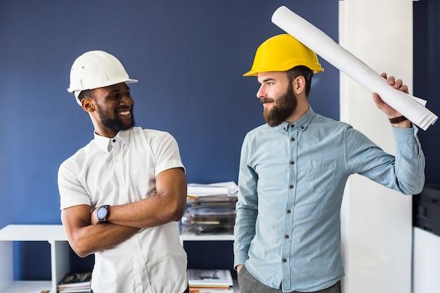 Zwei junge männliche glückliche architekten, die spaß im büro machen