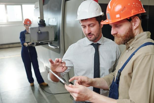 Zwei junge männliche ingenieure zeigen auf technische daten auf dem tablet-display, während sie details der präsentation beim treffen besprechen