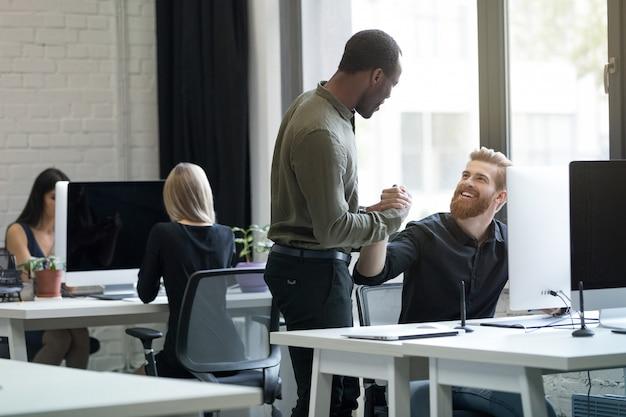 Zwei junge männliche kollegen diskutieren über neues startup-projekt