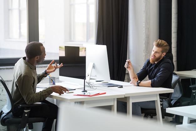 Zwei junge männliche kollegen sitzen an gegenüberliegenden schreibtischen