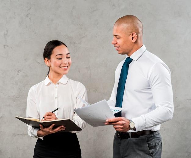 Zwei junge männliche und weibliche führungskräfte, die das dokument gegen graue wand besprechen