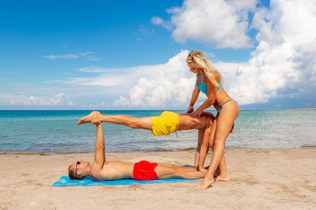 Zwei junge mann und frau am strand machen fitness yoga übung zusammen. acroyoga-element für kraft und gleichgewicht.