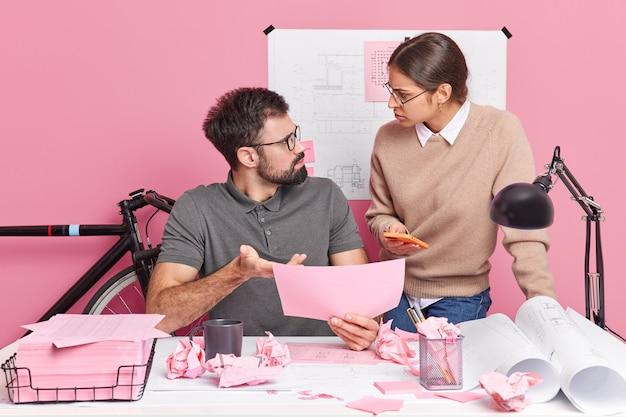 Zwei junge mitarbeiterinnen und mitarbeiter sehen sich verärgert die schuld für die fehlerpose am modernen schreibtisch an und diskutieren die skizze für das bauprojekt. professionelle ingenieure arbeiten gemeinsam an blaupausen