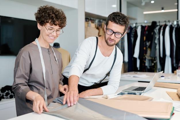 Zwei junge modedesigner wählen textilien für eines ihrer neuen saisonkollektionen