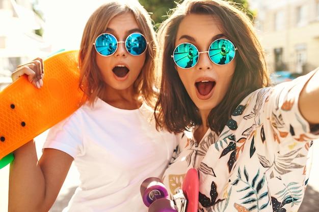 Zwei junge modelle im sonnigen sommertag, die selfie-fotos machen