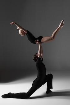 Zwei junge moderne balletttänzer auf grau