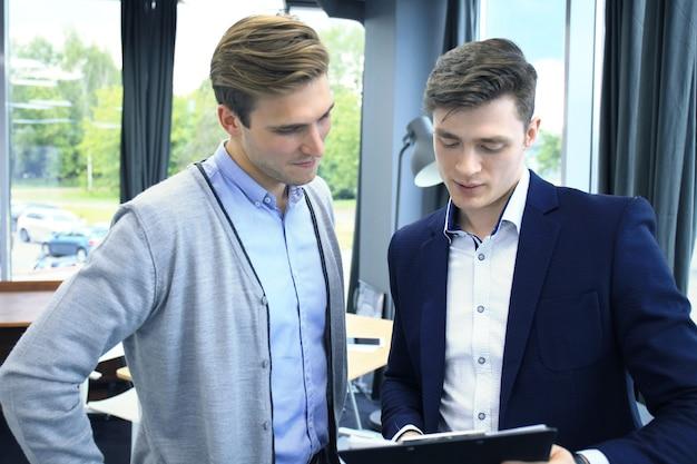 Zwei junge moderne männer diskutieren über die arbeit im büro.