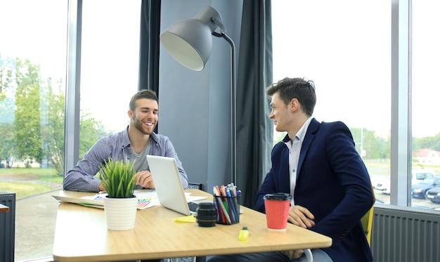 Zwei junge moderne männer diskutieren über die arbeit im bürostudio.