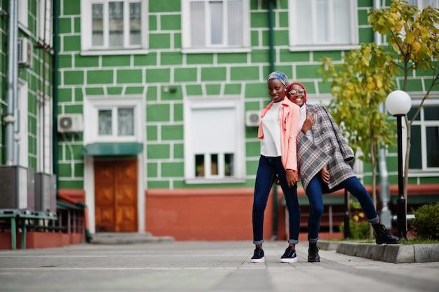 Zwei junge moderne modische, attraktive, große und schlanke frauen in hijab und mantel posierten