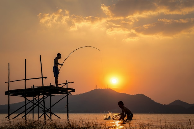 Zwei junge nette jungen, die an einem see an einem sonnigen sommertag fischen.