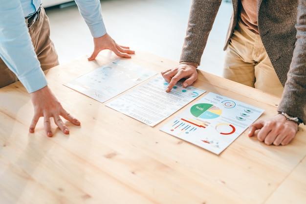 Zwei junge ökonomen in abendgarderobe beugen sich während der diskussion der daten über finanzpapiere auf einem holztisch