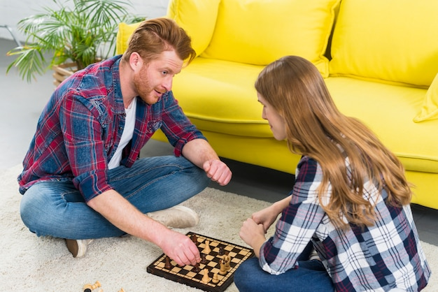 Zwei junge paare, die das schach im wohnzimmer spielen
