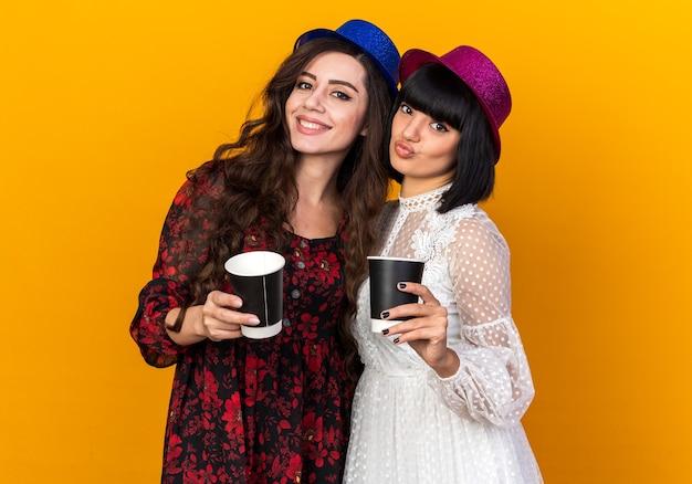 Zwei junge partygirls mit partyhut, die beide eine plastikkaffeetasse halten, lächeln einander und schürzen die lippen isoliert auf oranger wand