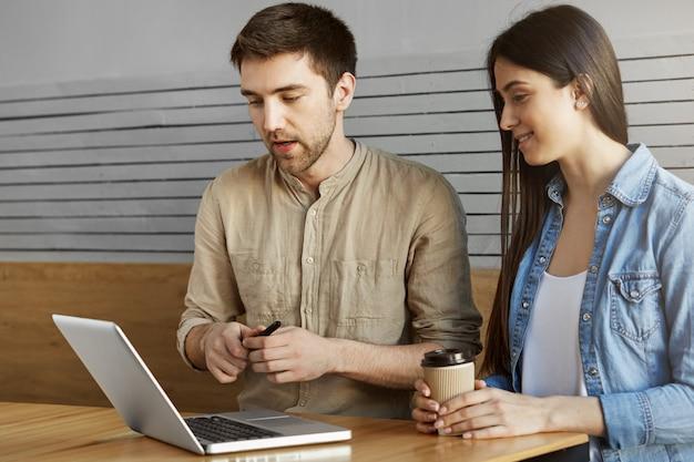 Zwei junge perspektive startup-enthusiasten, die im café sitzen, kaffee trinken, über arbeit sprechen und projektdetails auf laptop-computer durchsehen. entspannende und produktive zeit