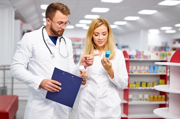 Zwei junge professionelle drogistenkollegen, die ein rezept erfüllen