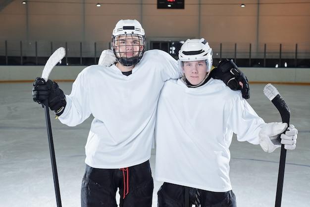 Zwei junge professionelle hockeyspieler in sportuniform, handschuhen und schutzhelmen, die stöcke halten, während sie nach dem spiel auf der eisbahn stehen