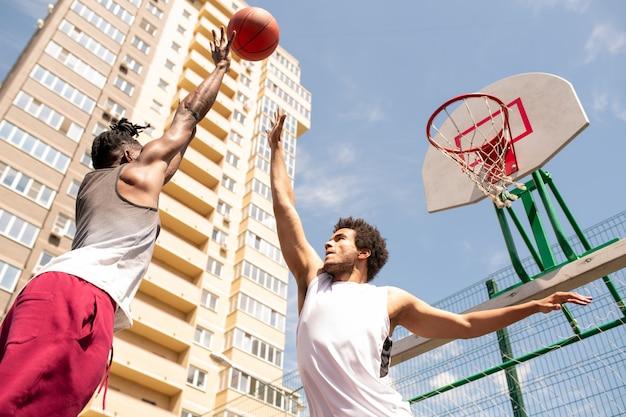 Zwei junge professionelle interkulturelle basketballspieler in aktivkleidung, die versuchen, den ball zu fangen