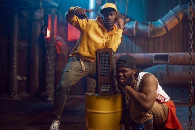 Zwei junge rapper, breakdance im studio mit cooler underground-dekoration