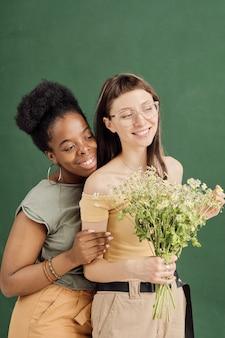 Zwei junge romantische lesbische dates mit blumen stehen vor der kamera
