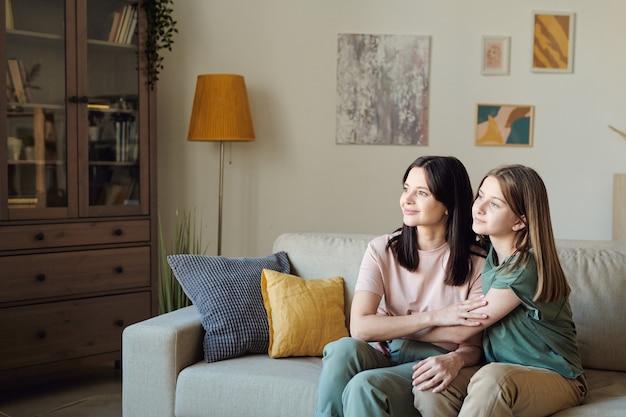 Zwei junge, ruhige frauen, mutter und tochter, die durch ein großes fenster im wohnzimmer schauen, während sie dicht beieinander auf der couch sitzen