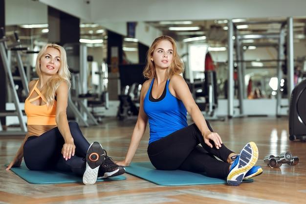 Zwei junge schlanke blonde frauen, die übungen im fitnessstudio machen