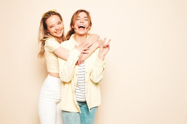 Zwei junge schöne blonde lächelnde hippie-frau in trendiger sommerkleidung