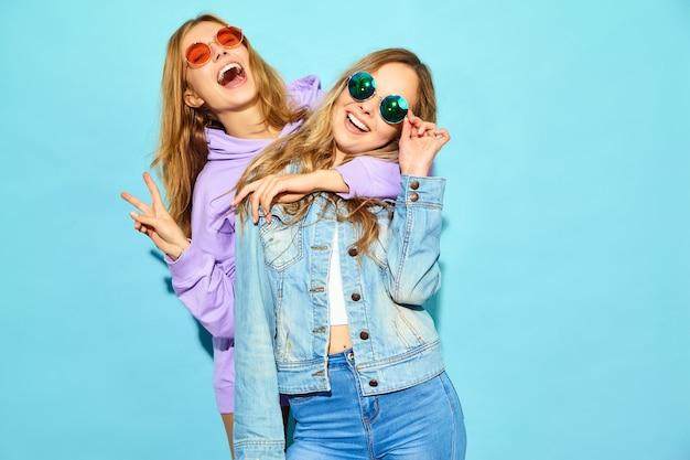 Zwei junge schöne blonde lächelnde hippie-frauen im modischen sommer kleidet. sexy sorglose frauen, die nahe blauer wand in der sonnenbrille aufwerfen. positive models werden verrückt und umarmen sich