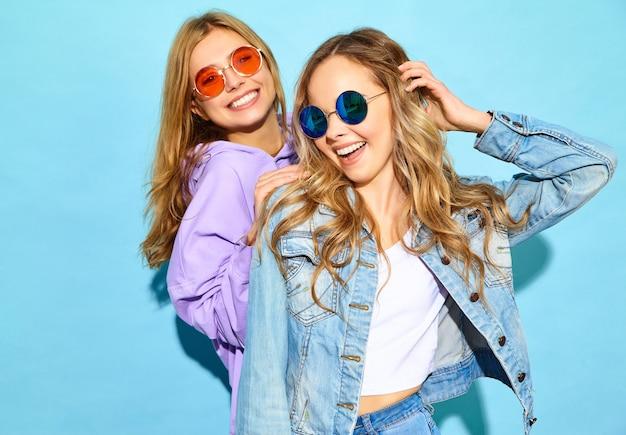 Zwei junge schöne blonde lächelnde hippie-frauen im modischen sommer kleidet. sexy sorglose frauen, die nahe blauer wand in der sonnenbrille aufwerfen. positive models werden verrückt