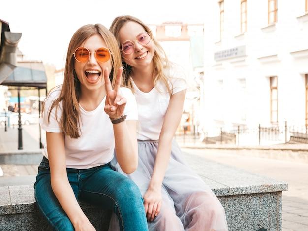 Zwei junge schöne blonde lächelnde hippie-mädchen im weißen t-shirt des modischen sommers kleidet. frauen sitzen auf der straße. positive modelle, die spaß in der sonnenbrille haben. zeigt friedenszeichen
