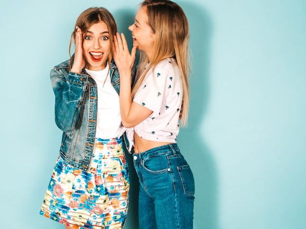 Zwei junge schöne blonde lächelnde hippie-mädchen in der zufälligen kleidung des modischen sommers.