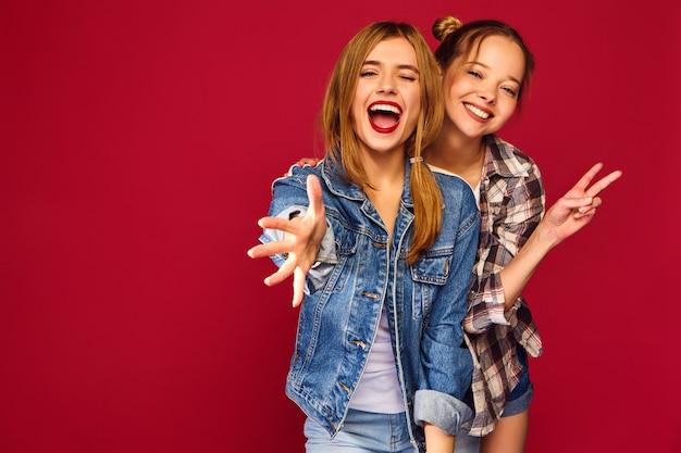 Zwei junge schöne blonde lächelnde hipster-frauen, die in den trendigen sommerlichen karierten hemdkleidern aufwerfen