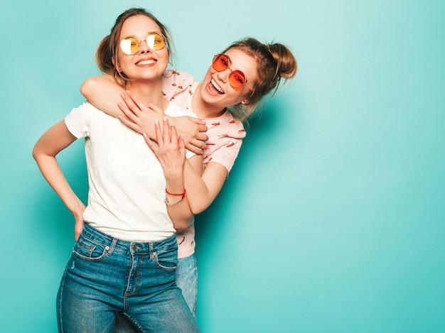 Zwei junge schöne blonde lächelnde hipster-mädchen in trendigen sommer-hipster-jeans-kleidern. sexy sorglose frauen, die nahe blauer wand aufwerfen. trendige und positive models, die spaß haben