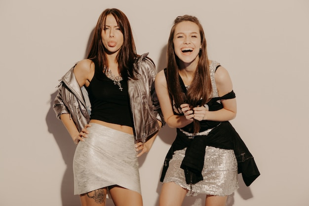 Zwei junge schöne blonde lächelnde hipster-mädchen in trendigen sommerkleidern. sexy sorglose frauen, die nahe wand im studio aufwerfen. positive modelle, die spaß haben