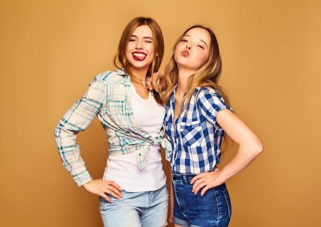 Zwei junge schöne blonde lächelnde im trendigen karierten sommerhemden