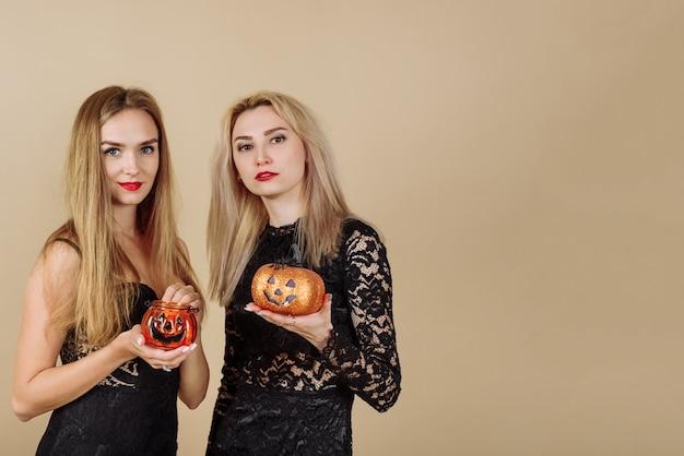 Zwei junge schöne blondinen halten kürbisförmige süßigkeitenkörbe auf einem beigen hintergrund. halloween und werbekonzept.