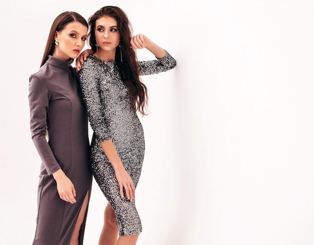 Zwei junge schöne brünette mädchen im schönen trendigen sommer glänzenden kleid