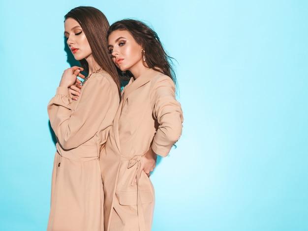 Zwei junge schöne brünette mädchen in der schönen trendigen sommerkleidung. sexy sorglose frauen, die nahe blaue wand im studio aufwerfen
