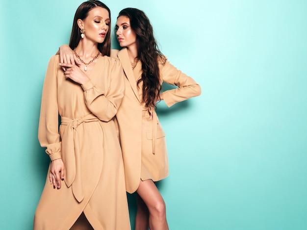 Zwei junge schöne brünette mädchen in schönen trendigen sommer ähnlichen anzügen kleidung. sexy sorglose frauen posieren in der nähe von blauen wand im studio