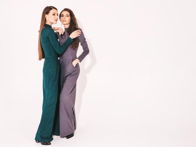 Zwei junge schöne brünette mädchen in schönen trendigen sommeranzugkleidung