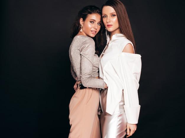 Zwei junge schöne brünette mädchen in schönen trendigen sommerkleidern. sexy sorglose frauen, die über schwarz im studio posieren
