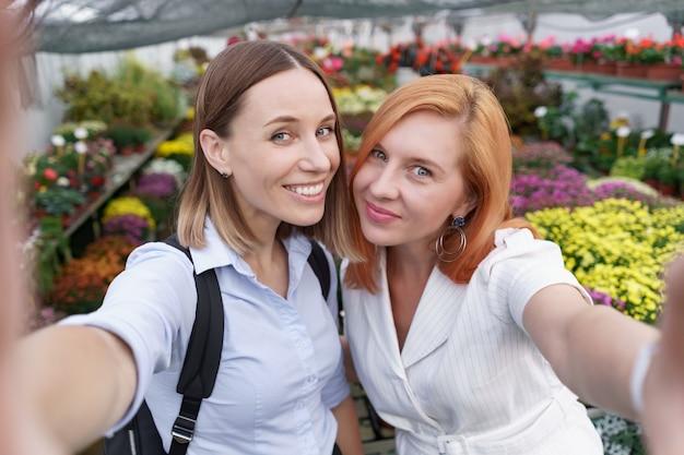 Zwei junge schöne damen machen selfie auf blumenhintergrund im gewächshaus