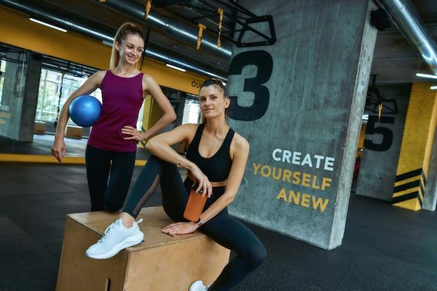 Zwei junge schöne fitness-mädchen in sportkleidung stehen im crossfit-fitnessstudio und schauen in die kamera und
