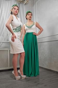 Zwei junge, schöne frau, brünette, blondine in weißen kurzen kleidern