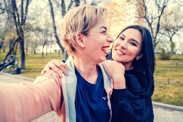Zwei junge schöne frauen, enge freunde verschiedener nationalitäten, lachen und machen ein selfie im park, einem europäischen und asiatischen freundschaftstag