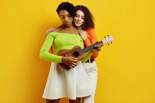 Zwei junge schöne frauen im bunten sommer kleidet mit kleiner gitarre