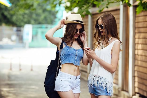 Zwei junge schöne frauen laufen durch die stadt und hören musik