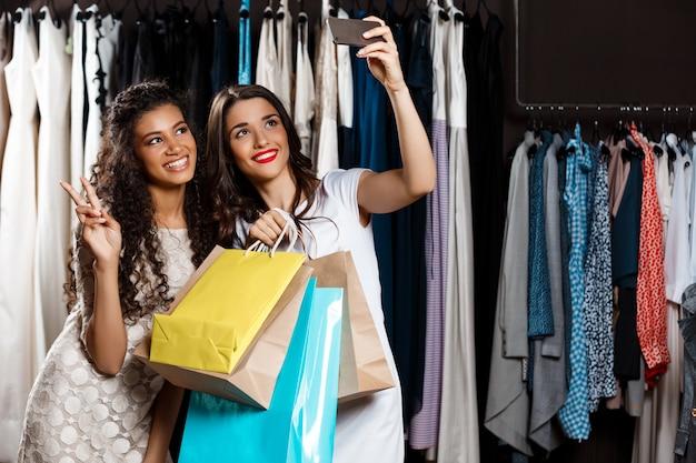 Zwei junge schöne frauen machen selfie im einkaufszentrum