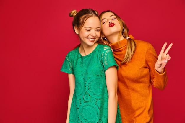 Zwei junge schöne frauen posieren in trendigen kleidern