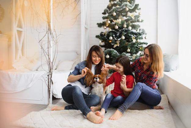 Zwei junge schöne frauen und kleines mädchen, während weihnachten zu hause feiern